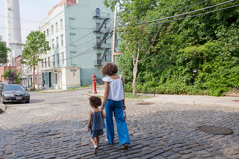 A Mother and daughter walking down an urban street