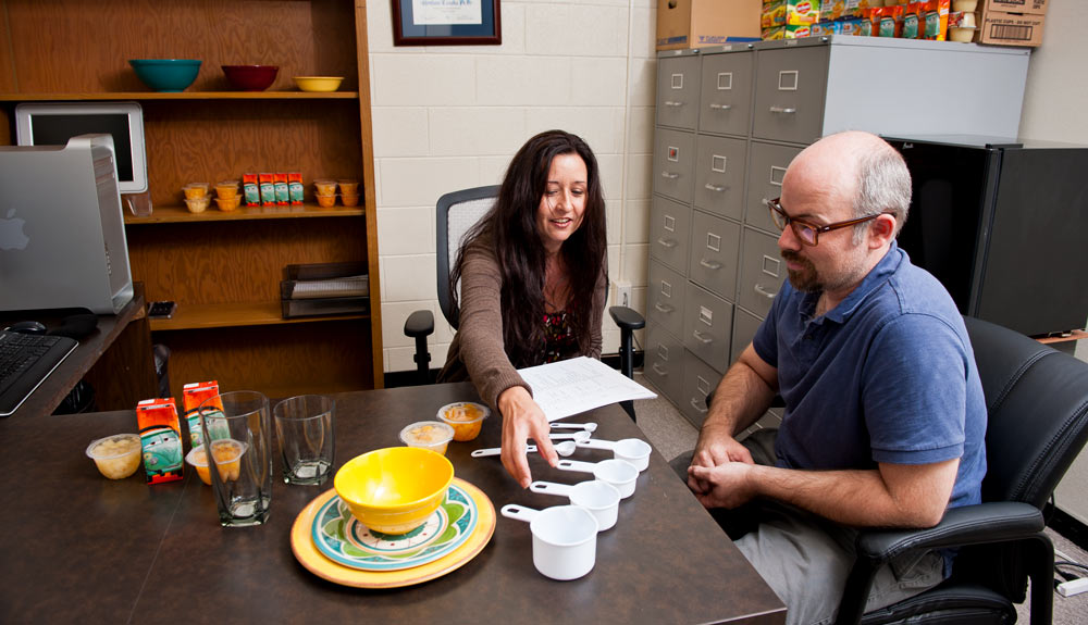 Two people sitting at a desk with measuring cups and fruit