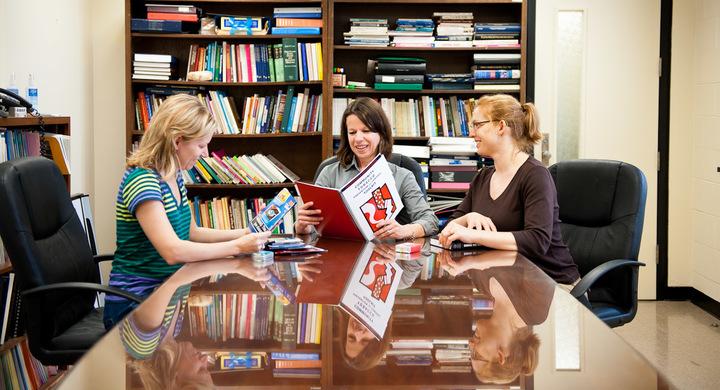 Three professors sitting around a table
